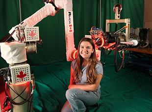 PEY Co-op student Erin Richardson standing next to autonomous robot